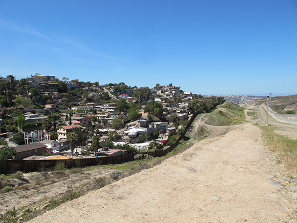 A view from between the U.S. border walls of a Tijuana neighborhood known as Colonia Libertad, one of the last stops in Mexico for many border crossers | Photo: Jena Lee.