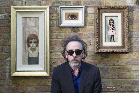 """Big Eyes"" director Tim Burton posing with Margaret Keane paintings. 