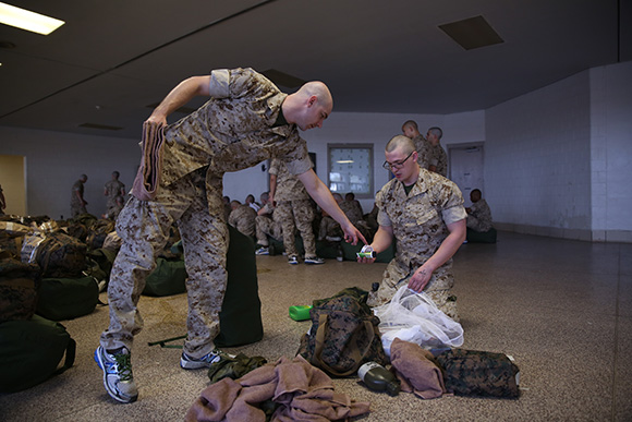A Marine Corps recruit instructs another how to organize his things. | Photo:  Cpl. Octavia Davis, United States Marine Corps.