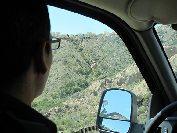 "Our driver, a CBP agent, looks out at Smugglers Gulch where a ""spotter's hut"" is nestled in the hillside. 