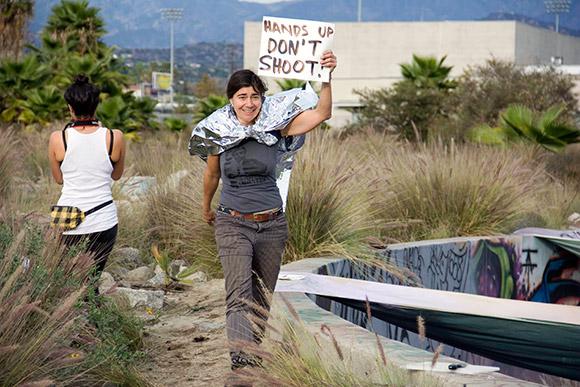 Koumoundouros holding up protest signs while walking the roundhouse | Photo: Carren Jao