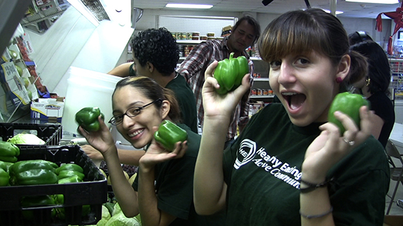 Healthy Eating Active Community Youth Ambassadors Magali Bravo and Brittani Marie Dighero, high school students at The Accelerated School High School, stocking produce at Los Compadres Market.