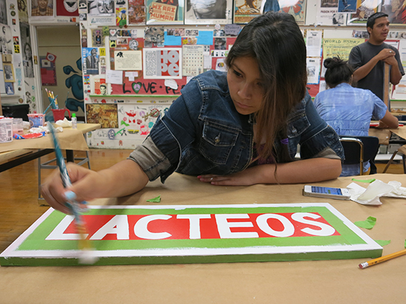 Community Liaison Shirley hand-painting a sign for Sociedad Market, August 2013.