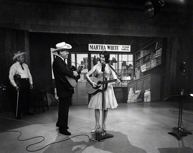 Earl Scruggs and June Carter on the set of the Flatt & Scruggs Grand Ole Opry Show, 1961. Paul Warren (in background), fiddler, Foggy Mountain Boys. © Les Leverett