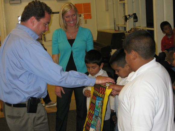 Children are presenting a story quilt they created to San Diego School Board Member Richard Barrera.
