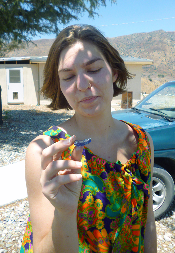 Annie Danis studies a piece of blue glass found at the Hog Farm site, perhaps a medicine bottle, or maybe a fragment of some psychedelic wonderkey-juju-whosamowhatsis. | Photo: Courtesy of Robby Herbst.