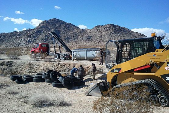 BLM officials cleaning up an illegal tire dump on public lands.   Photo: Courtesy BLM.