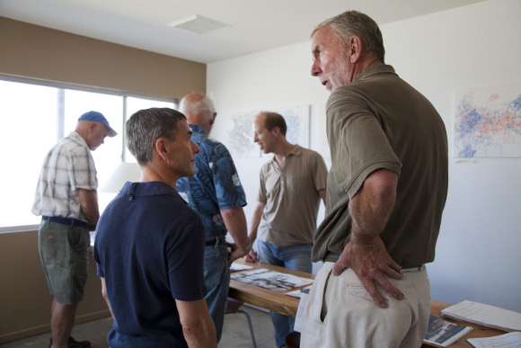 Bernard Leibov (left) talking with local sculptor, Steve Rieman (right) at BoxoHouse. May 2012 resident artist, Tim Saternow is at back behind table in middle. |  Photo: Kim Stringfellow.