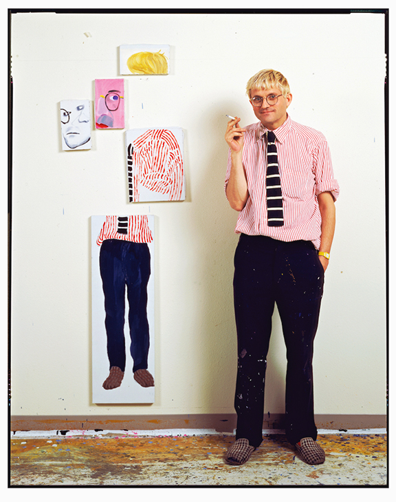 """David Hockney, next to a similar cubist painting of himself in his Hollywood Hills studio, 1984. Titled """"David Hockney - Hollywood Hills studio,"""" 1984. 