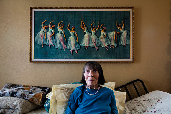 Marta Becket (with one her paintings behind her) photographed at her home at Death Valley Junction on November 28, 2015. | Photo: Kim Stringfellow.