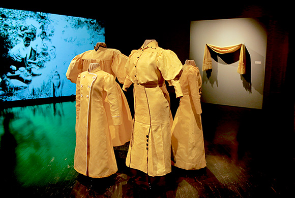 "Installation view, Nao Bustamante, ""Soldadera"" at the Vincent Price Art Museum. Foreground: ""Kevlar Fighting Costumes"" (set of 5), 2015. Background: ""Soldadera,"" film projection, 2015. 