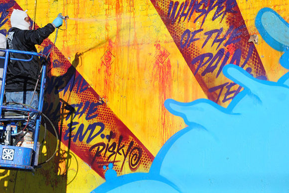 Final touches on RISK's mural on the border of the Arts District and Skid Row   Photo: MOCA.