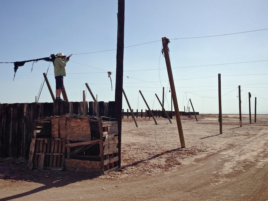 Photographer on desert ruin capturing first image in article. Salton Sea, CA. 2014. | Photo: Christopher Langley.