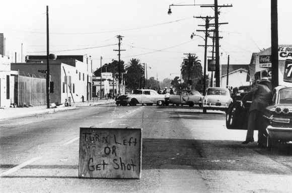"August 1965: A makeshift sign urging drivers to ""Turn Left Or Get Shot"" during the race riots in the Watts area of Los Angeles. 