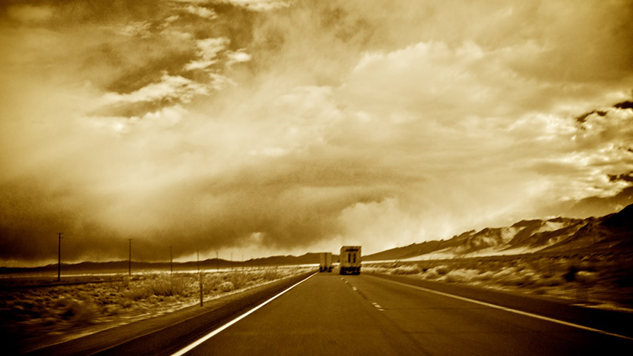 Twin Trucks Heading South on Highway 395 Towards Storm - Infrared Exposure - Owens Valley, CA - 2013 | Photo: Osceola Refetoff