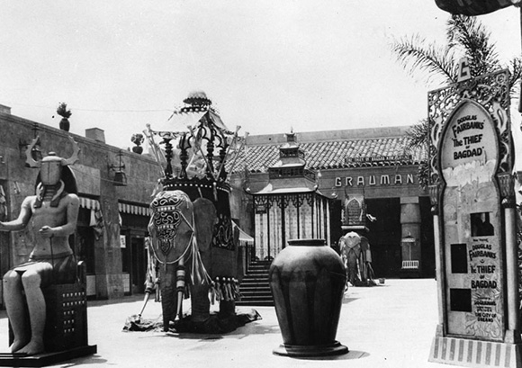 """A view of the courtyard of Grauman's Egyptian Theatre with statues of an Egyptian king, Indian elephants. Billboard advertising for Douglas Fairbanks """"The Thief of Bagdad."""" The theatre opened in 1922."""