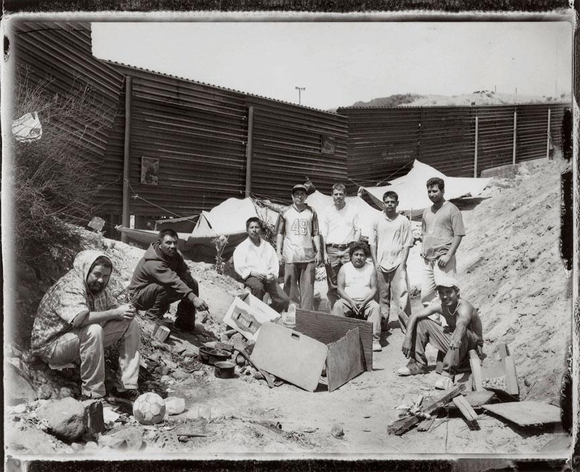 Turounet (third from right, top row) with a group of men that assisted him in installing some of his border 'retablo' photographs onto the U.S.-Mexico border fence, Mexico side. | Photo: © 2012 Paul Turounet.