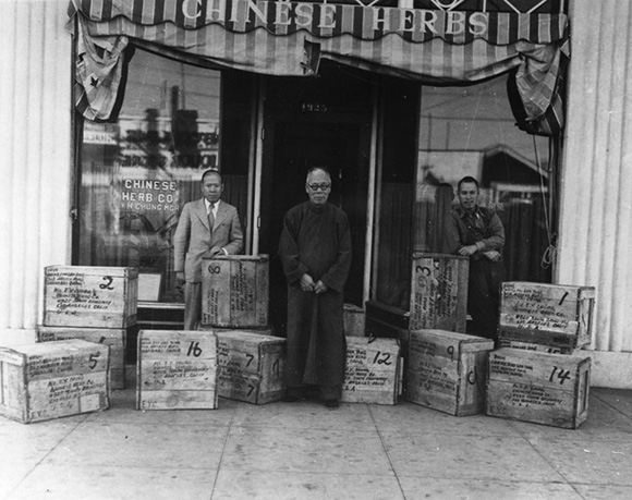 The exterior of the Chinese Herb Company at 4925 South Broadway in Los Angeles. The proprietors  Yick   Hong , center, and his sons Elbert, left, and Sam stand among boxes shipped from China. | Courtesy of the Los Angeles Public Library