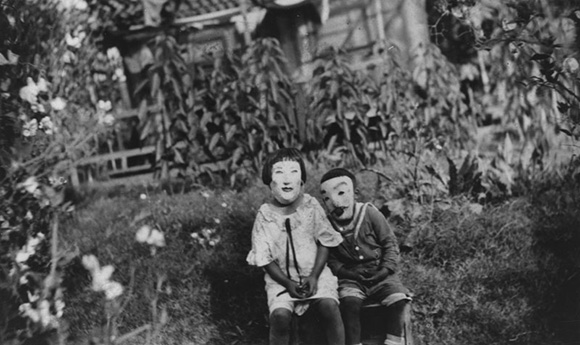 Aiko, left, and her brother Isamu wear  Halloween  masks as they sit in the yard of their home at a flower nursery, Flower View Gardens, a family business, on Los Feliz Boulevard. | Courtesy of the Los Angeles Public Library