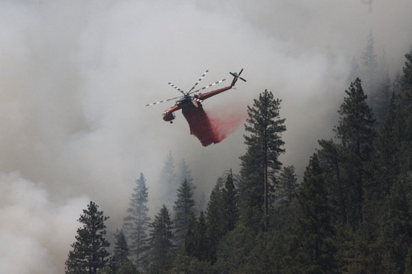 A helicopter assists fire crews on the ground. | Photo: Sean Collins/Inciweb
