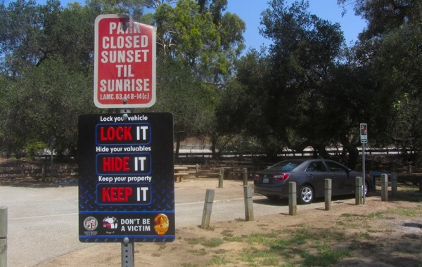 A sign advising visitors of best practices at the entrance of a Griffith Park parking lot. | Photo: Zach Behrens/KCET