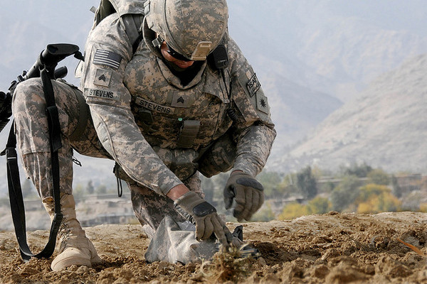 A horticulturist with the California Army National Guard's 40th Infantry Division Agribusiness Development Team gathers a soil sample from a field alongside the main road in Afghanistan.
