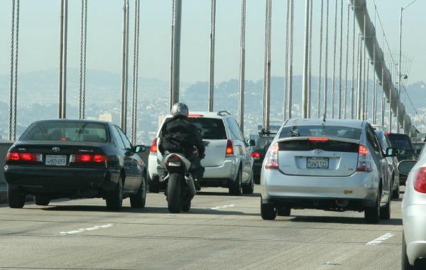 A motorcyclist lane splits on the Bay Bridge in San Francisco.