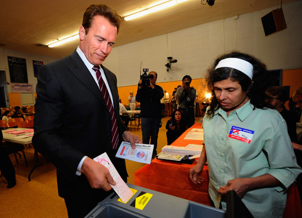 Calif. Gov. Arnold Schwarzenegger votes under the supervision of poll worker Dhun May in the midterm election on Nov. 2, 2010 in Los Angeles. (Photo: Kevork Djansezian/Getty Images)