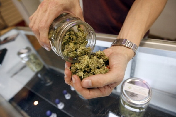 A budtender pours marijuana from a jar at Perennial Holistic Wellness Center medical marijuana dispensary, which opened in 2006, on July 25, 2012 in L.A. | Photo: Photo by David McNew/Getty Images