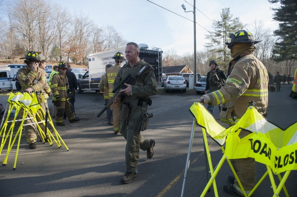 Connecticut State Police walk near the scene of an elementary school shooting in Newtown, Connecticut. | Photo by Douglas Healey/Getty Images