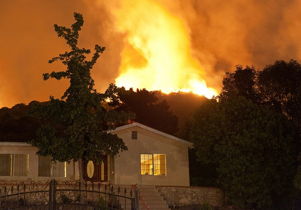 The 2009 Station Fire burns behind a home in La Crescenta, CA.