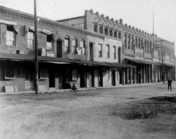 "Exterior of two earlier constructions in Chinatown. On the shorter building hangs a banner that reads ""A Los Cultos Espanoles."" 