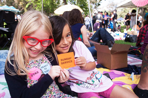 Kids giving away free stickers from Sunday Service at Dyke Day   Photo: Maya Santos
