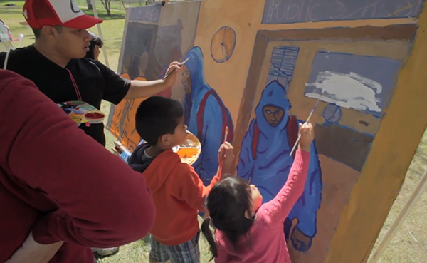 Community members paint a mural depicting the school to jails pipeline at the Saludarte event