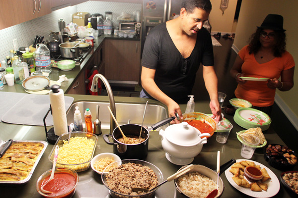 Host Ramy Eletreby sets up the Iftar (breakfast) with traditional Middle Eastern dishes. I Photo: Jonathan Olivares