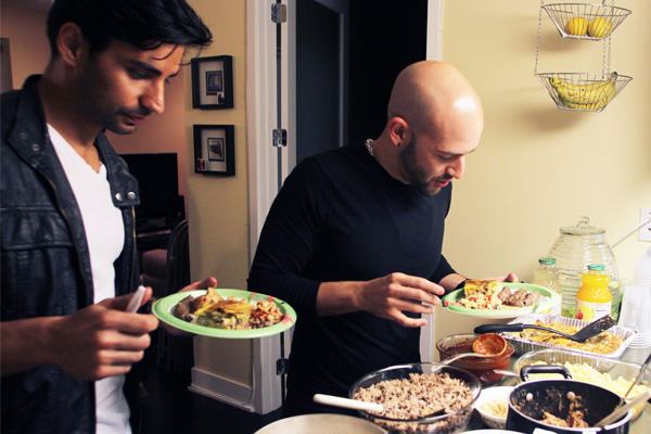 Jason Velazquez (right), a revert, samples traditional foods with his husband, Tony Follo (left) I Photo: Jonathan Olivares