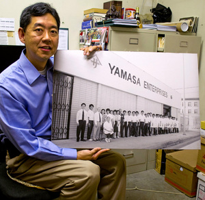 Teiji Kawana holds an old photo of Yamasa Enterprises, where his office is located | Photo by Sarah Silcox