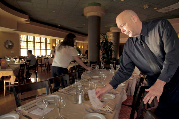 Manager David Lee sets up a table at Pat's Restaurant