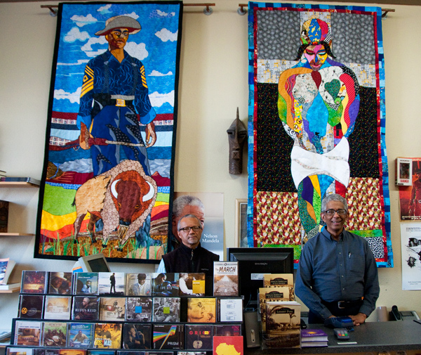 Co-Proprietors Tom Hamilton and James Fugate in front of a two tapestries by Leimert Park artist Ramsess. | Photo: Alvaro Parra