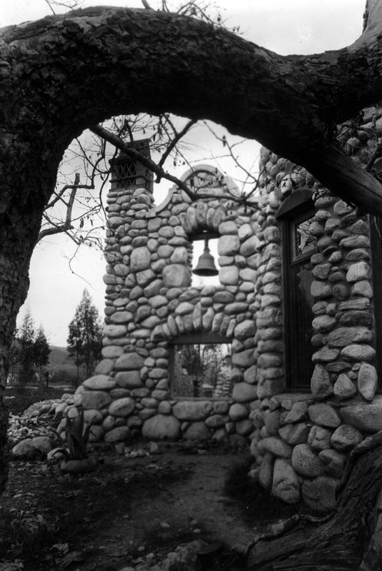 Exterior view of Charles Lummis' house, showing the belfry and chimney, under a tree limb | Photo: LAPL