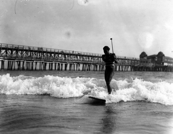 Duke Kahanamoku practises his golf swing while riding his surfboard towards shore. A long pier stretches outwards in the background, ca. 1925 | Security Pacific National Bank Collection, Los Angeles Public Library