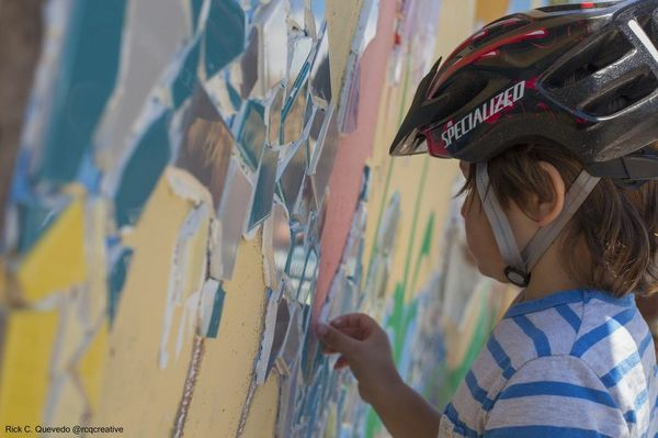 A young bicyclist is one of many who stopped during their ride to add tile to the ARTree tile mosaic mural being installed on South Fork Trail
