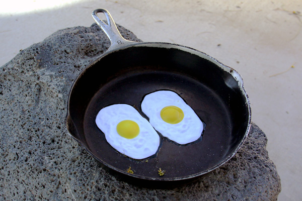 Sculpture of a pan with eggs frying, at the base of the thermometer