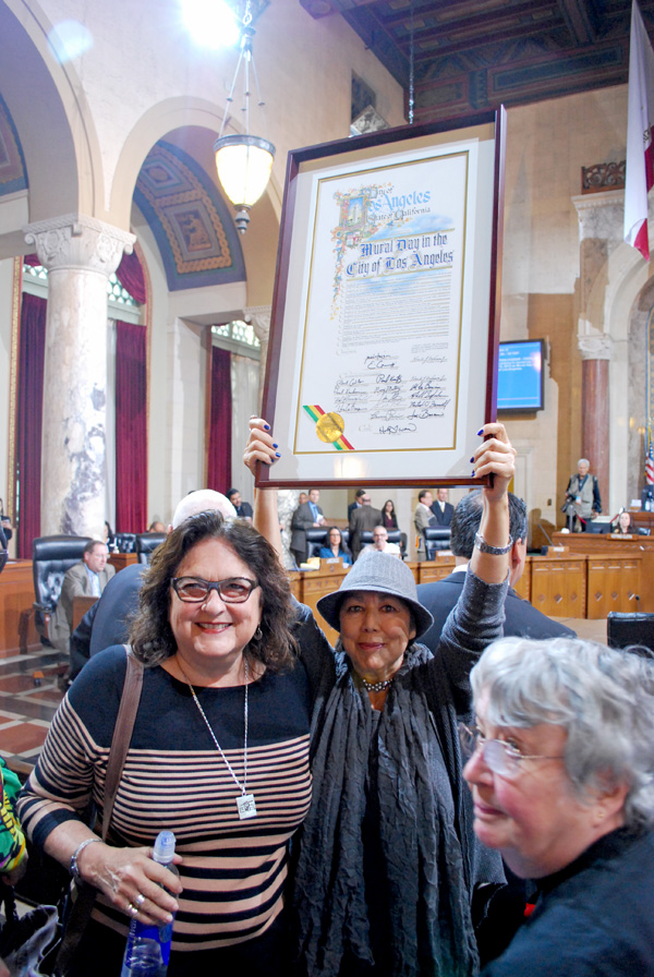 Rojas-Williams (center) holds up the proclamation of ''Mural Day in the City of Los Angeles. Muralists Judy Baca (left) and Emily Winters (right) look on I Photo: MCLA
