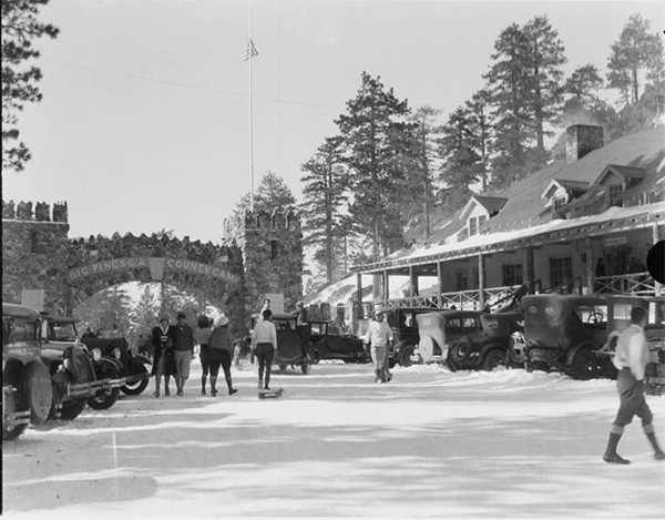 People and automobiles near the arch-entrance to Big Pines Recreational Camp. | Digitally reproduced by the USC Digital Library; From the California Historical Society Collection at the University of Southern California