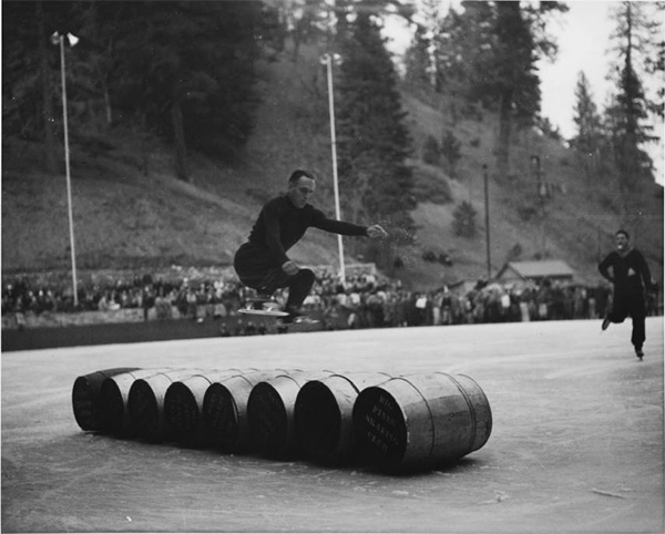 An ice skater performing jumps over a row of barrels at Big Pines mountain camp, ca.1930 | Digitally reproduced by the USC Digital Library; From the California Historical Society Collection at the University of Southern California