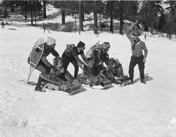 Three people being pushed down a hill on toboggans at Big Pines. | Digitally reproduced by the USC Digital Library; From the California Historical Society Collection at the University of Southern California