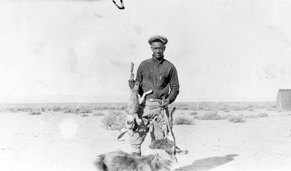 A hunter named Kirk poses with his brace of rabbits as his dog looks on. | Courtesy of the Los Angeles Public Library