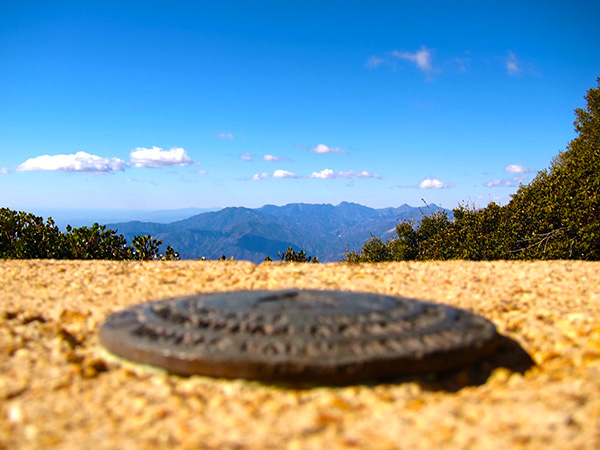 A geographic marker on the remains of a concrete pier on Lookout Mountain points to the summit of Mount Wilson | Photo: Daniel Medina