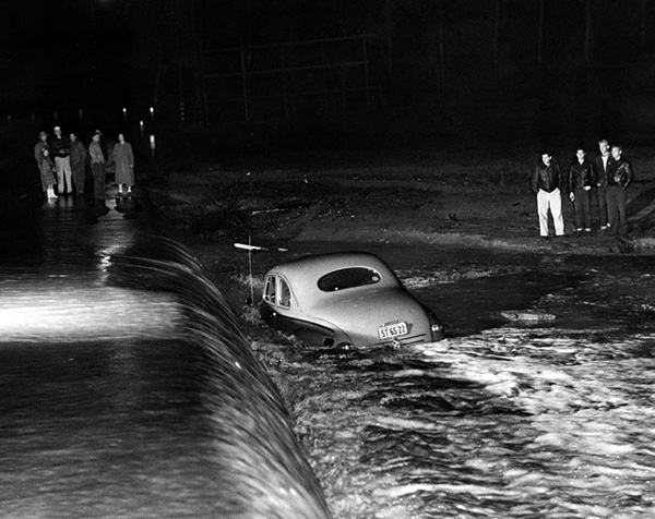 Mrs. Irene Henry was saved from drowning when her car was washed off the road and into the flooded Río Hondo River. Bystanders look at her car stuck in the river. | Photo Courtesy of the Los Angeles Public Library